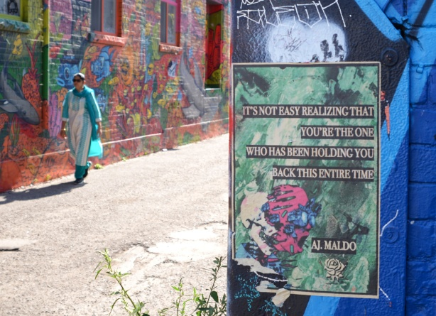 on a wall in Graffiti Alley, a poster with a saying or perhaps poes credited to A.J. Maldo, with a woman in a turquoise sari walking past