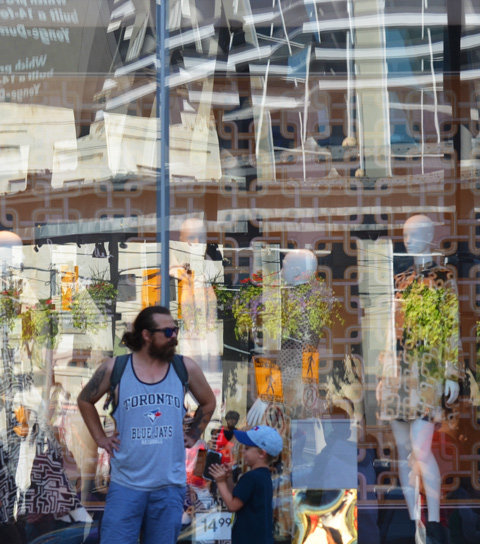 a father and son stand in front of a large store window with lots of reflections. Father is wearing a Toronto blue jays shirt