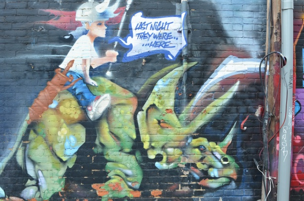 old mural on a wall in Milky Way alley, a young girl is riding on the back a dinosaur, with words that say was last night they were here