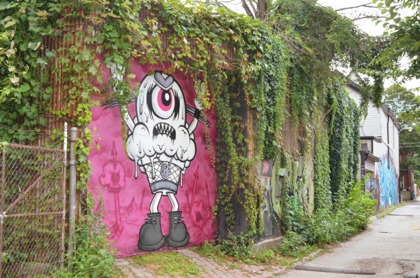 large gate (or garage door) in an alley painted pink with a painting of a one eyed monster on it