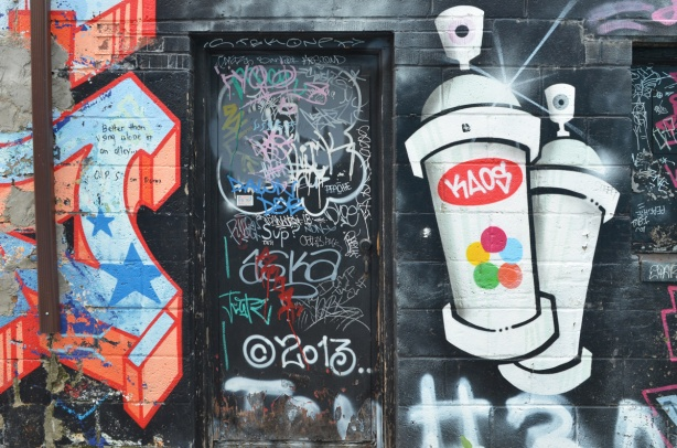 black door and wall in Milky Way lane, with graffit on the door, painting of two spray paint cans on the right side of the door, kaos brand. text graffiti on the left side in orange and white