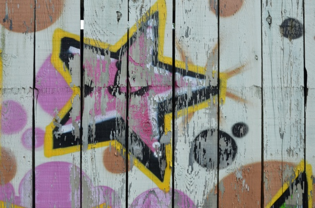 faded street art, wood grain of wood fence showing through. pink star with black sides to look 3 D, outlined in yellow