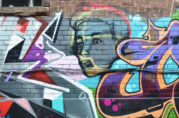 woman's face as part of a mural in Milky Way alley, text mural around her