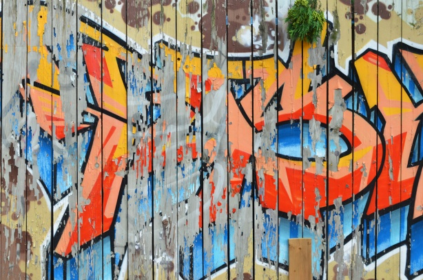 paint peeling off wood fence, street art painting only partilly still there