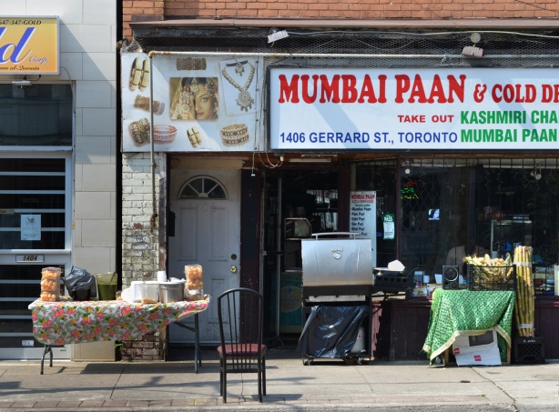 Mumbai Paan shop on Gerrard Street in Little India with a barbeque on the sidewalk, a bucket of corn and a pile of sugar cane