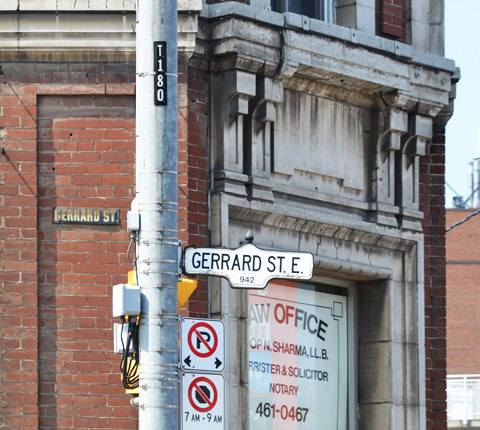 side of an old brick building with stone features, an old street sign on the building Gerrard Street, now a law office with signs in the windows