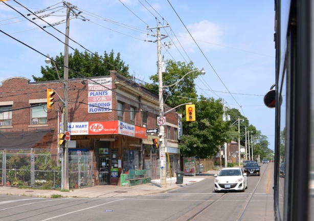 picture taken out the window of a streetcar on Gerrard, an older 2 storey brick building with retail on the lower level, two large old wood hydro poles