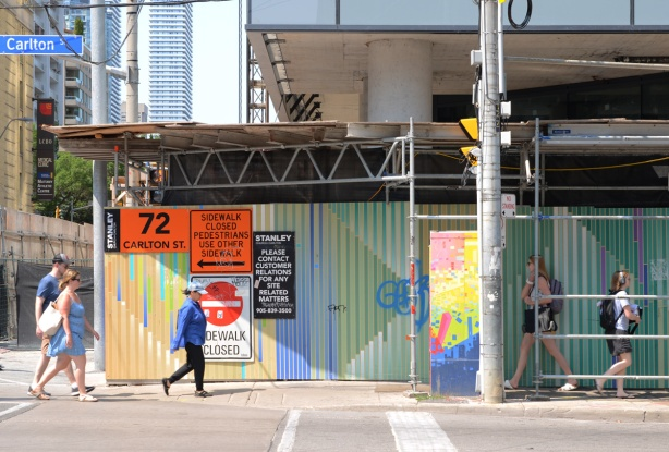 people walking past painted hoardings in front of a construction site, painted in stripes