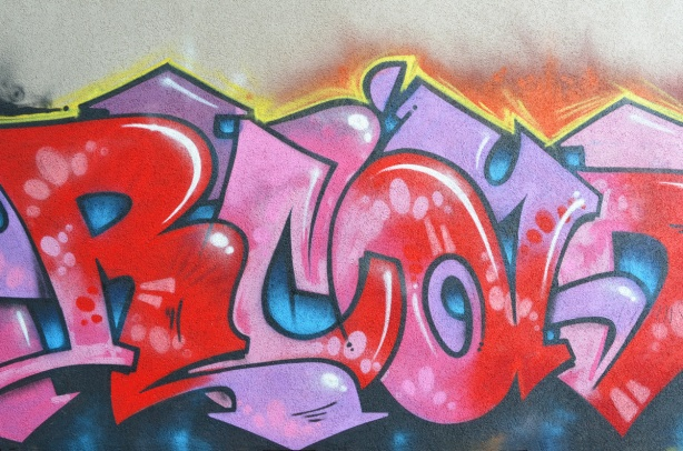 text graffiti mural in pinks and reds on blue background, in an alley,