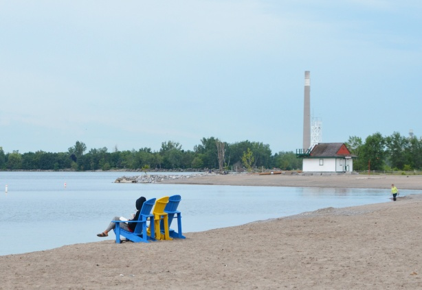 a person in a black hoodie is sitting on a blue Muskoka chair, reading a book on the beach