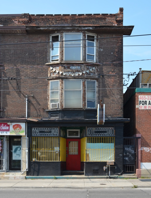 old three storey brick building with big bay windows on the upper two floors. Ground floor is a store or restaurant with bright red door and yellow metal bars over the windows