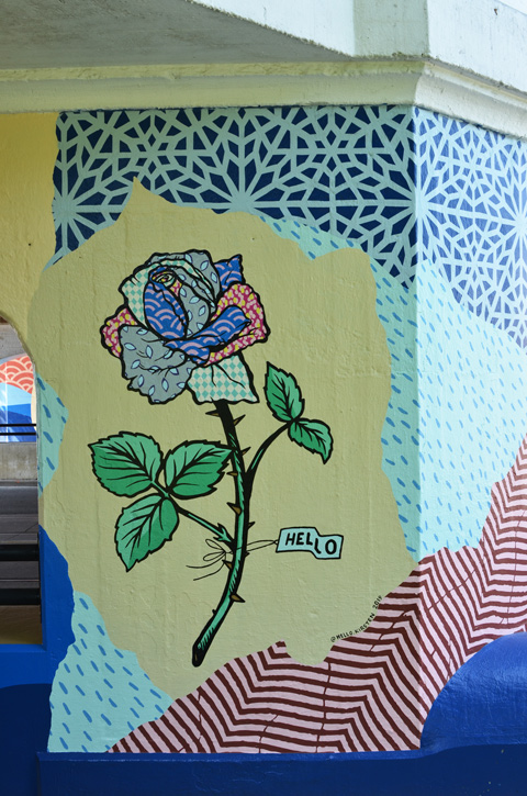 painting on a concrete pillar of a railway overpass, a rose with leaves, stem, and thornes, a collage of abstract shapes and