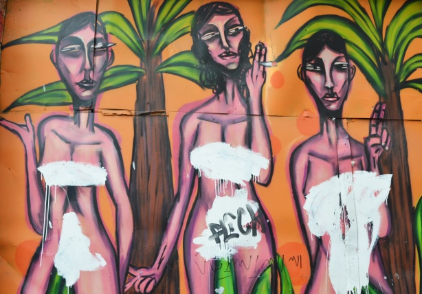 part of a mural of 3 nude pink and purple women, tall and skinny by palm trees, orange background, in an alley, the women have been painted over in white to cover breasts