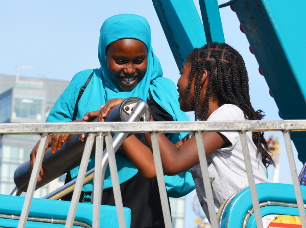 two young girls waiting to go on a midway ride, smiling, one is wearing a bright turquoise head scarf