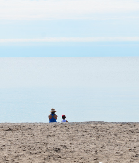 a mother in wide brimmed hat and her son in a red hat sit by the shore, sand, water, sky,