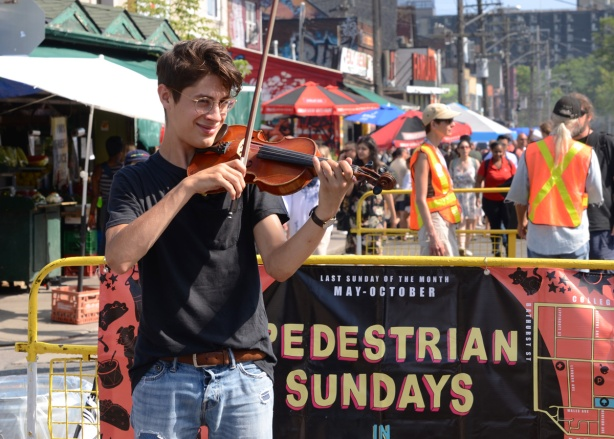a young man plays a violin in front of a pedestrian Sunday banner