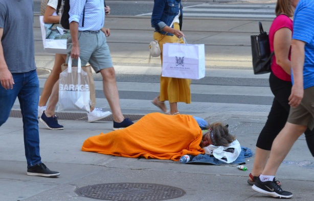 a man sleeps under a bright orange blanket on the sidewalk on Queen Street while people's feet pass by