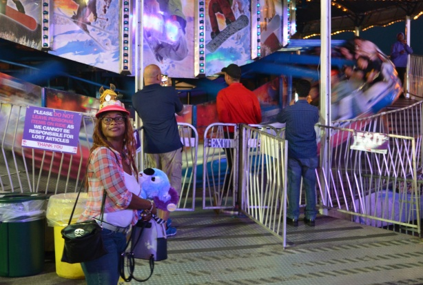 a woman wearing a hat and holding a blue teddy bear stands in front of a midway ride. A couple of people are taking pictures of the ride on their phones