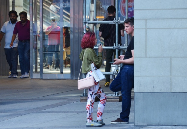 by one of the entrances to the Eaton Centre, outside, a man leans against a wall while a woman with reddish purple hair talks to him. She is wearing floral pants and has a pale pink handbag. Other people are coming out the doors of the Eaton Centre