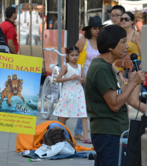 a woman talks into a microphone, about religion, a man sleeps on the sidewalk in the background as people and a TTC streetcar pass by. A mother and daughter are walking on the sidewalk and longing down at the sleeping man