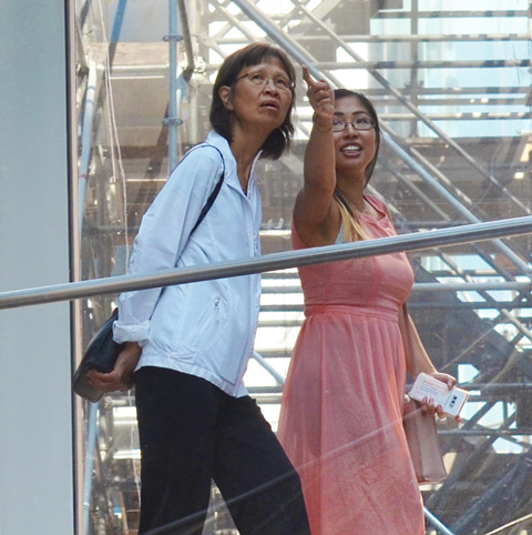 two women walking across the passage from the Eaton Centre to the Bay, over Queen Street. One is wearing a pink dress and is pointing to something. the other woman is trying to figure out what she is pointing at