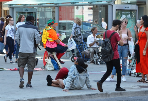 at the south west corner of Yonge and dundas, people. A man is playing drums, a woman sits on the sidewalk, other people are talking to each other, a man is dressed in outlandish clothes and is sitting on a stool giving out papers to those who pass by