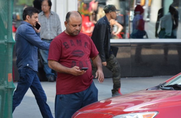 a man stands on the sidewalk beside a red car. He is looking at his phone. A man in the background leans against a store window, two other men are walking past