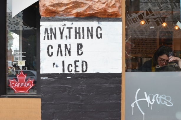 a sign stenciled beside a doorway that says Anything can b iced. Window beside it, with a woman sitting inside by the window