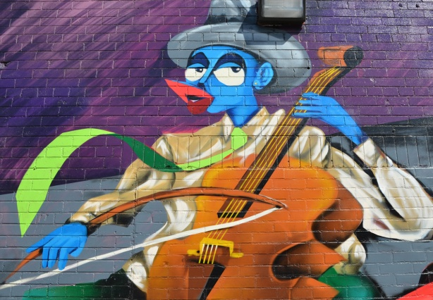 part of a mural, the band of story tellers, a group of musicians all with blue skin, bass player wearing a hat