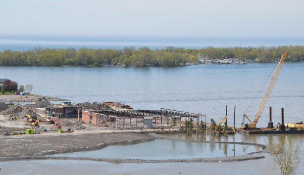 west end of portlands early on in the redevelopment process, partially demolished building, barge in water creating new land, reconfiguring the shoreline