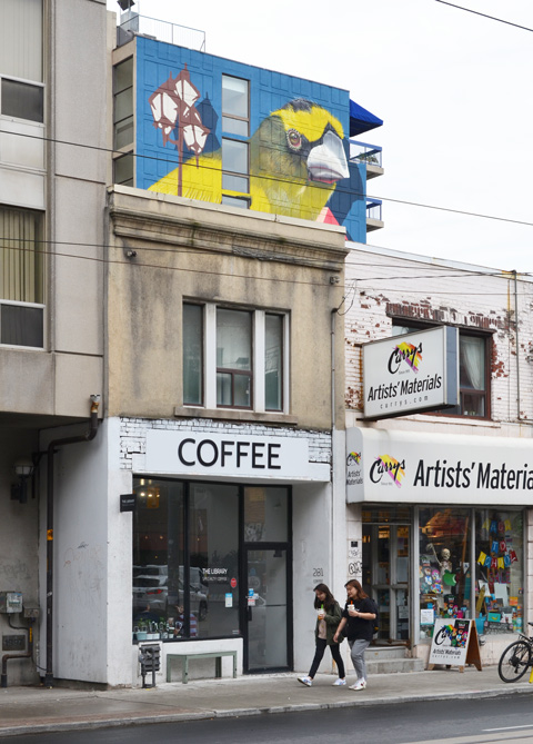 Dundas street, near McCaul, coffee shop and artist supply store, with a large mural by birdo above it