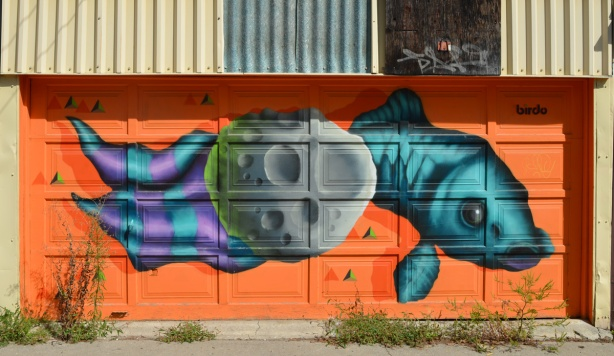birdo mural on a garage door, orange background, fish swimming behind a stone, fish is teal and tail is purple and teal striped