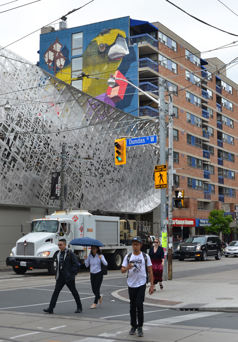 the corner of Dundas and McCaul with a large mural by birdo looking over it