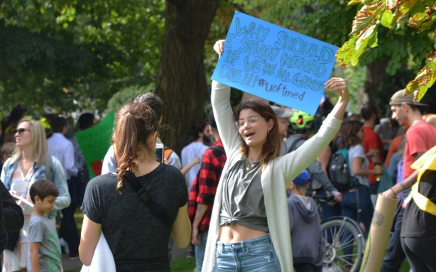climate strike, rally for action on climate change at Queens Park, a young woman with a blue sign poses for a photo being taken by a friend