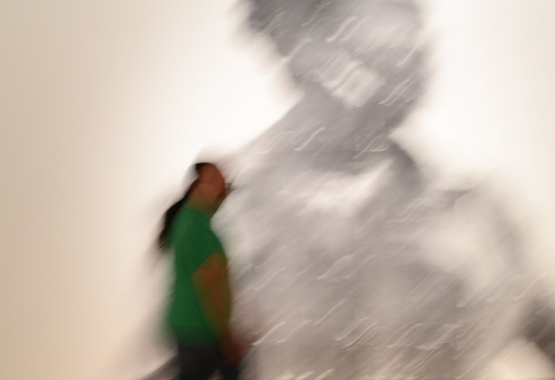 people, out of focus, walking past a large out of focus picture of a woman, a photo by Sandra Brewster as part of her blur series, a man in a green shirt