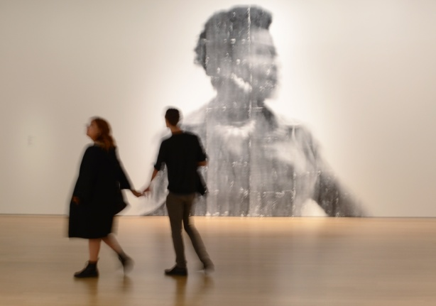 a couple holding hands with the woman leading the man, out of focus, walking past a large out of focus picture of a woman, a photo by Sandra Brewster as part of her blur series
