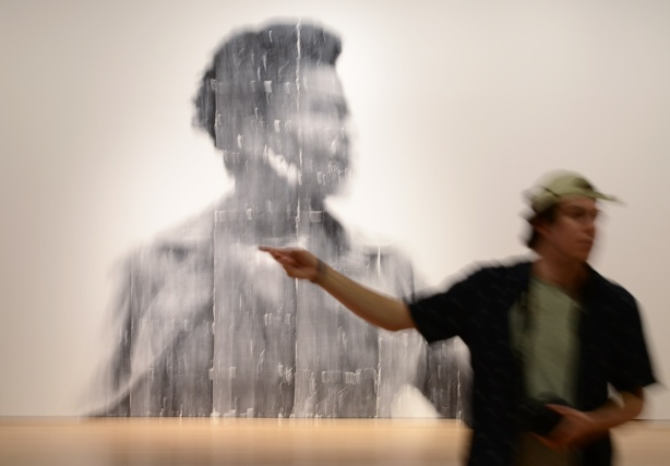 people, out of focus, walking past a large out of focus picture of a woman, a photo by Sandra Brewster as part of her blur series, a man pointing