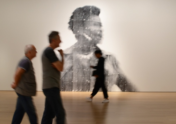 people, out of focus, walking past a large out of focus picture of a woman, a photo by Sandra Brewster as part of her blur series, three men, two are together and the third is walking in the opposite direction