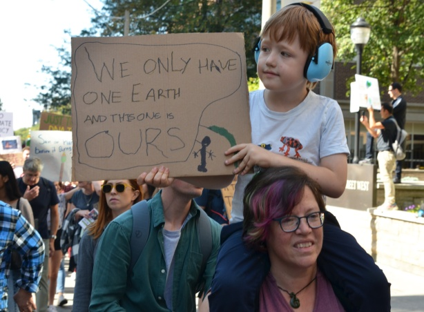 a boy with blue headphones is sitting on his mother's shoulders and holding brown cardboard sign that says We only have one earth and this one is ours