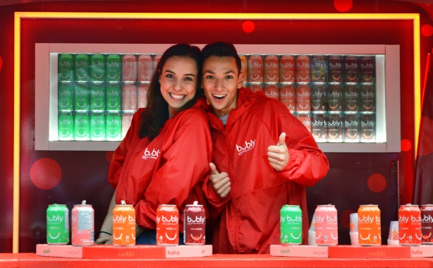 two young people working in a red booth for bubly drinks, both smiling and one is giving a thumbs up