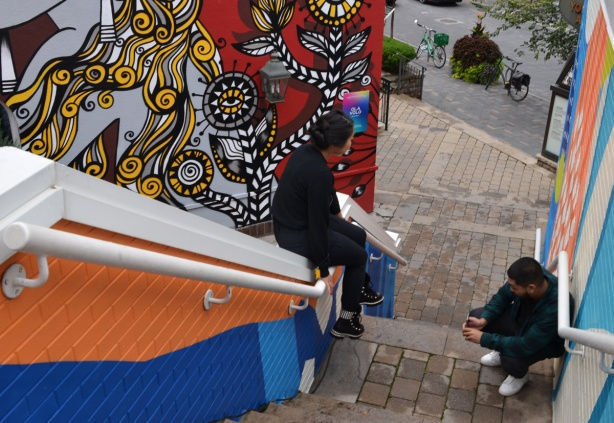 a young woman sits on the railing of an outdoor staircase that has been painted with street art. A man is taking a pictrure with his phone of her feet against the artwork
