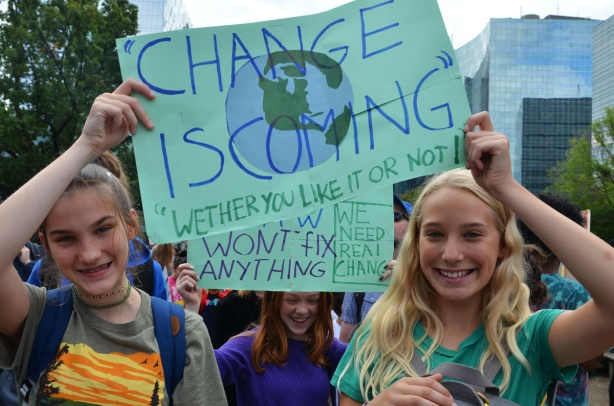 at the climate strike rally at Queens Park on a sunny morning in September, three girls with pale blue signs, Change is coming,