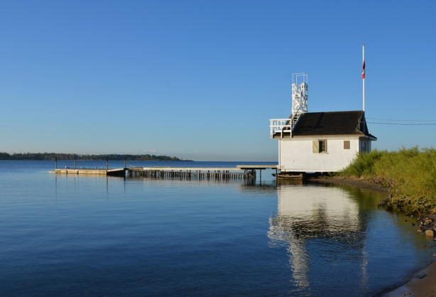 cherry lifeguard station, with dock in front, very calm and still water, reflections of the building in the water, early morning,