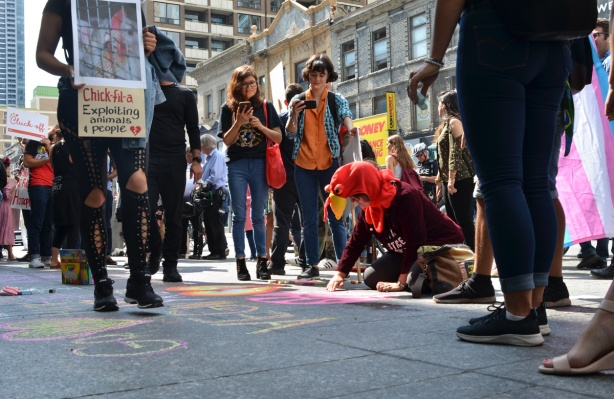 a woman with a chicken head costume on, draws with chalk on the sidewalk while other people stand around her