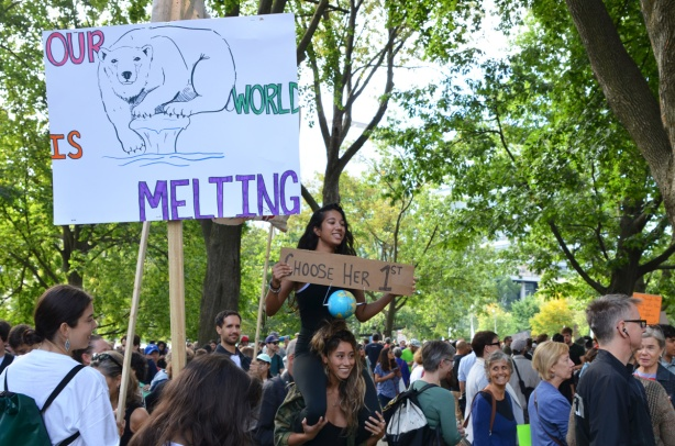climate strike, rally for action on climate change at Queens Park, a group by the trees in the park, two signs, one with a bear on it and words about melting ice. The other is being held by a woman who is on another person's shoulders