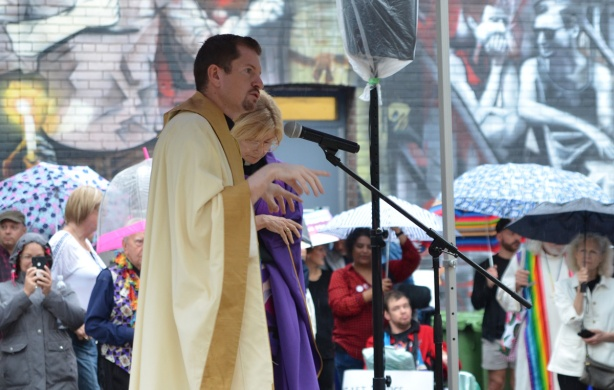 two Christian religious leaders talk at a rally