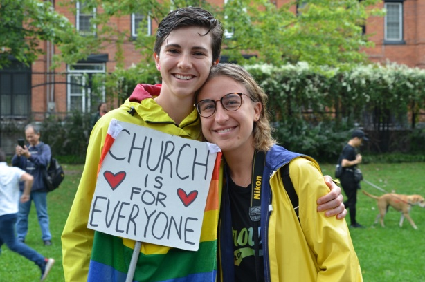 two women in yellow rain jackets holding a sign that says Church is for everyone