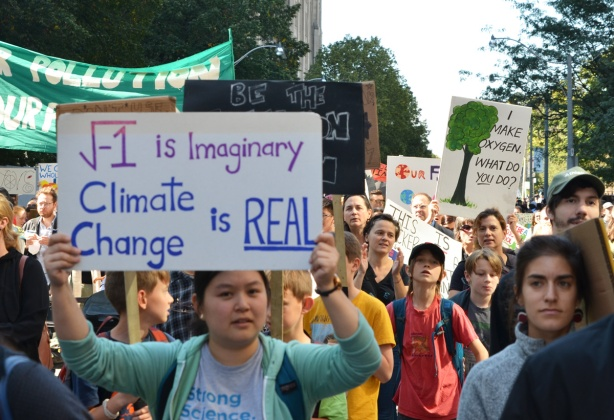 a woman holds a sign that says that the square root of negative 1 is imaginary but climate change is real, mathematics and science