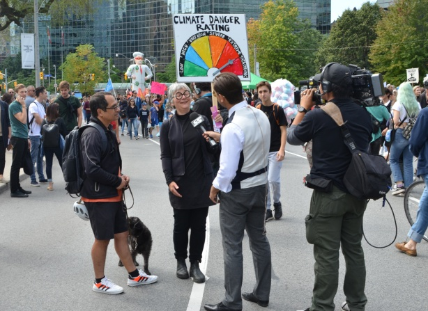 a woman is being interviewed for television, at a climate change protest,