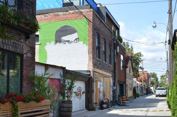Croft street alley with garages on the left, and apartments above some of them, a mural of a man's face where the bottom half has been painted over with white paint
